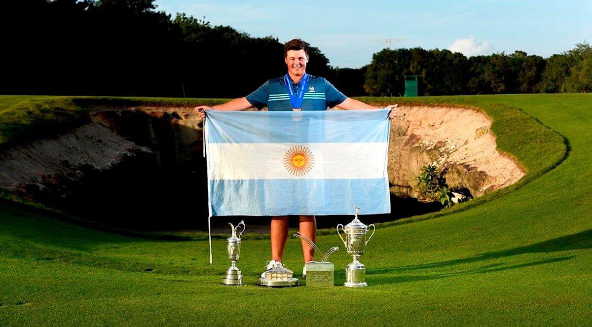 El golfista Abel Gallegos sostiene una bandera de argentina en el campo de golf. Debajo se ve el trofeo del Latin American Amateur Championship.